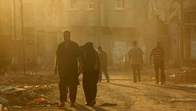 Palestinian walk through dust caused by demolished homes in the Gaza City neighborhood of Shijaiyah.