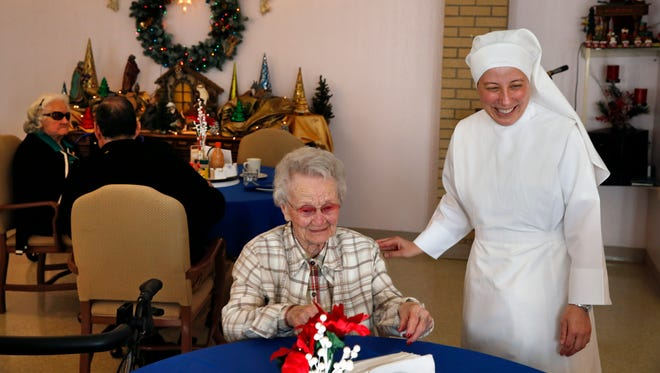 Sister Mary Grace visits with a resident at an elderly home run by Little Sisters of the Poor in Denver last month.