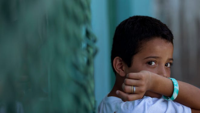 Edwin Lemus, 10, from El Salvador, sits in the men's section of a shelter providing temporary refuge to Central American migrants on their way north, in Arriaga, Chiapas State, Mexico.