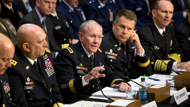 In this June 4, 2013 file photo, Joint Chiefs Chairman Gen. Martin Dempsey, center, testifies on Capitol Hill in Washington, before the Senate Armed Services Committee hearing investigating the growing epidemic of sexual assaults within the military. The number of reported sexual assaults across the military shot up by more than 50 percent this year. Defense officials suggest that victims are becoming more willing to come forward.
