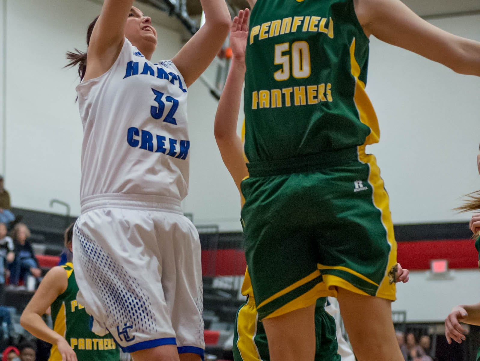 Pennfield's Rachel Swartz (50) blocks the shot of Harper Creek's Kelly Klutts (50) in first round of districts game at Marshall Monday evening.