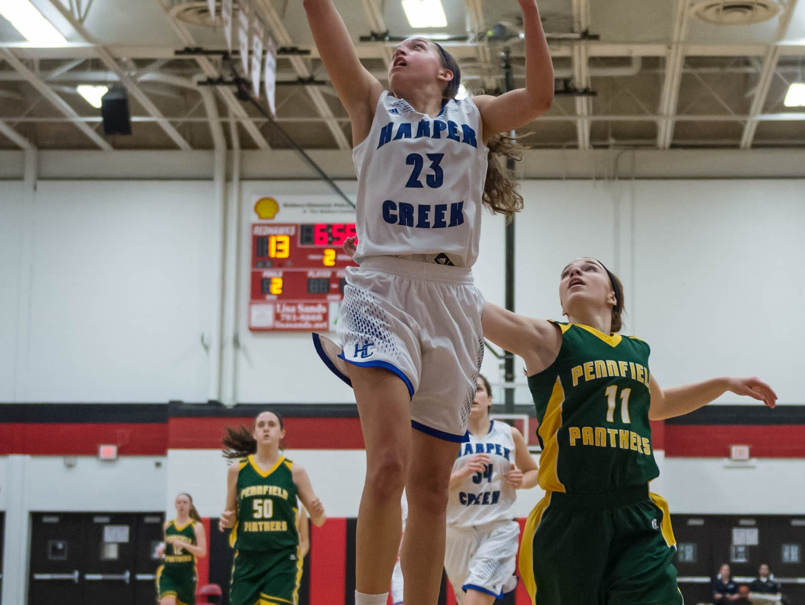 Harper Creek's Charley Andrews (23) goes for the layup in first round of districts game at Marshall Monday evening.