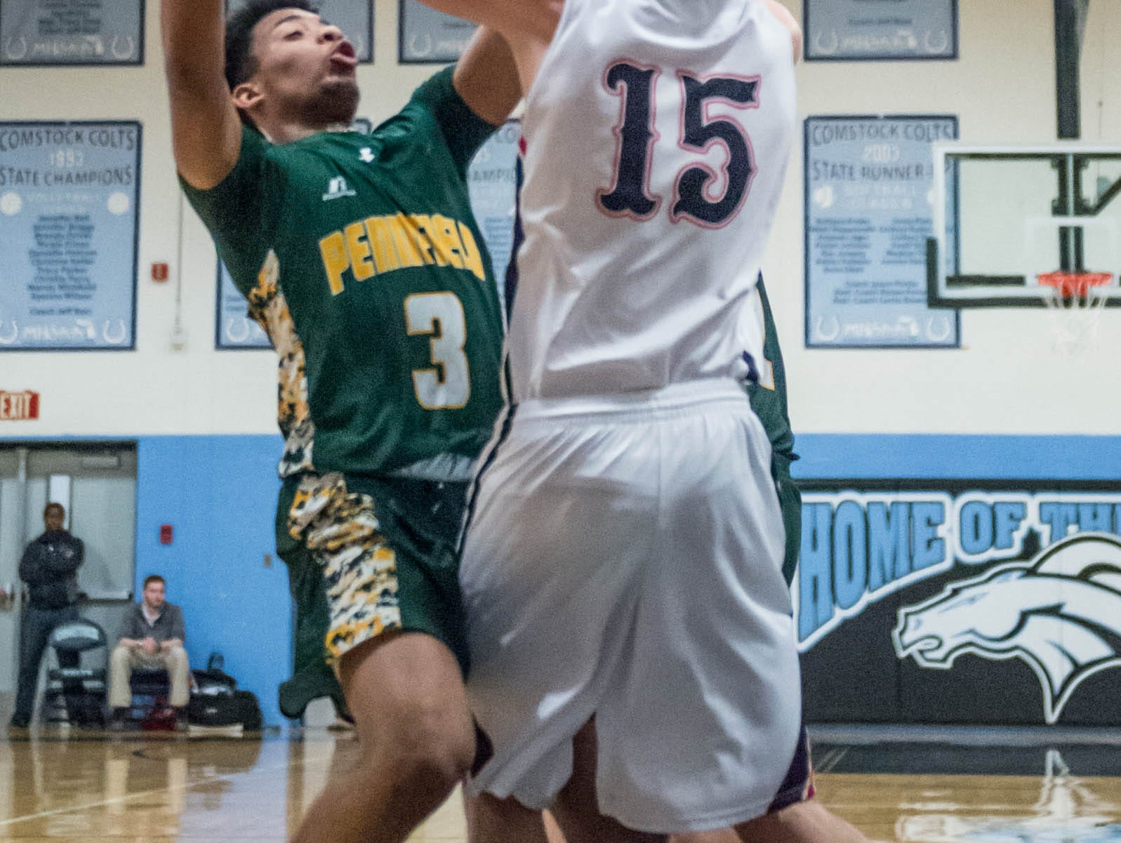 Marshall's T. J. Roco (15) goes to block Pennfield's Ronald Jamierson (3) shot during Monday's district game.