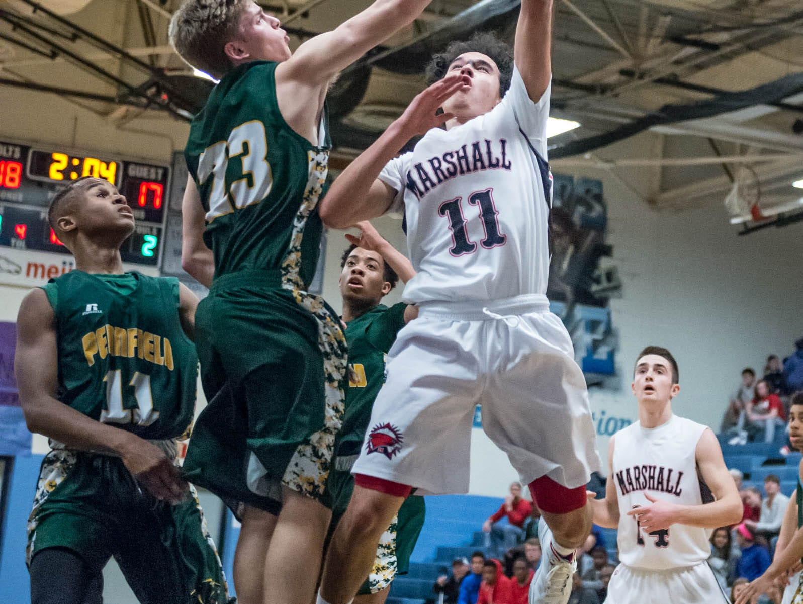 Marshall's Tyler Torrey (11) goes for the hoop while Pennfield's Grant Peterson (23) tries for the block during Monday's district game.