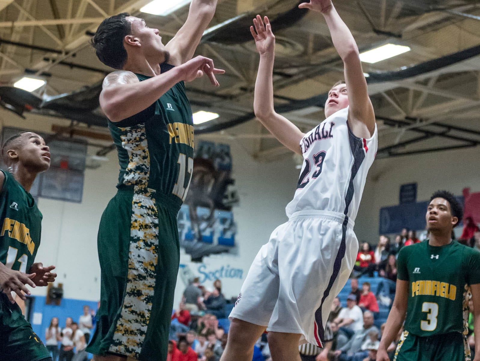 Pennfield's Steffen Kinne (12) goes for the shot block over Marshall's Cam Face (23) during Monday's district game.