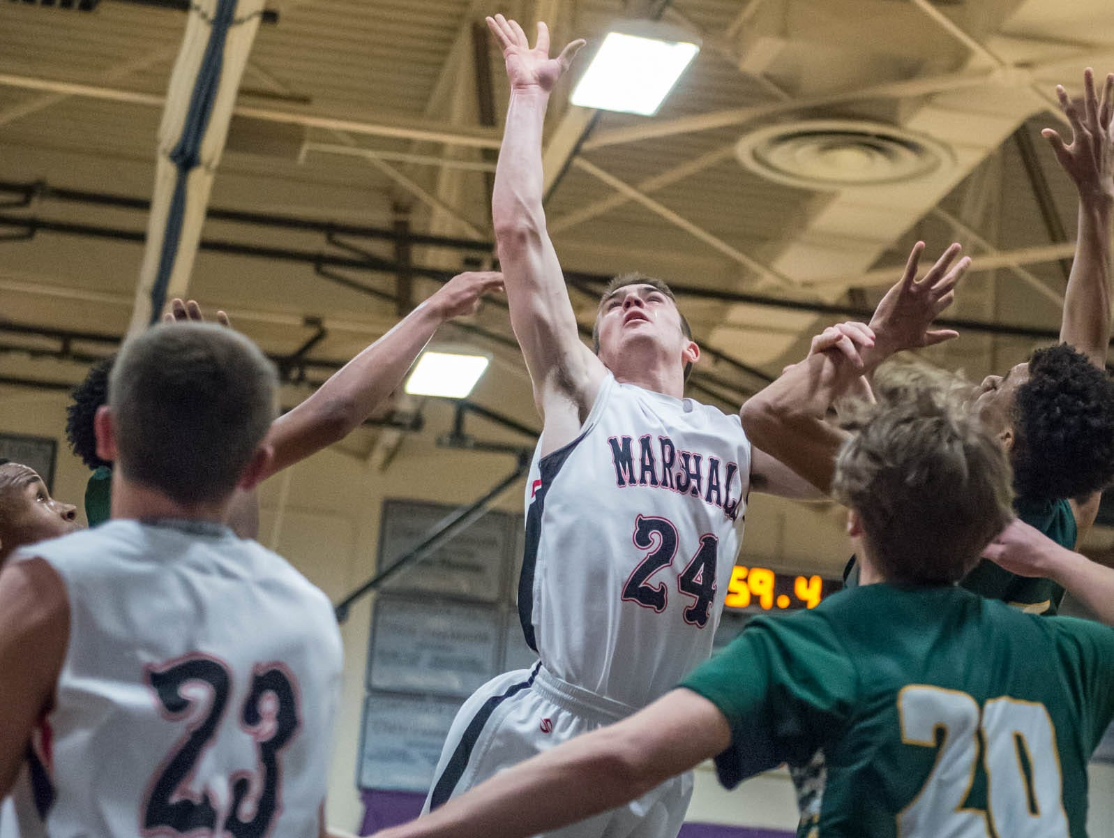 Marshall's Drew DeVine (24) goes for the hoop during Monday's district game against Pennfield.