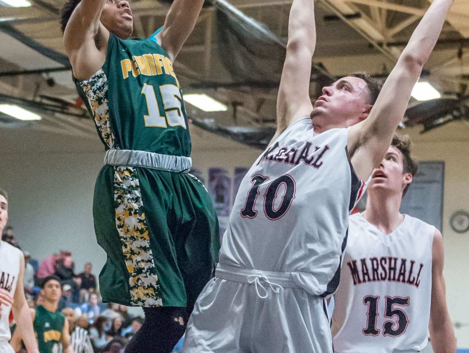 Pennfield's Domonick Gibson (15) goes for the hoop over Marshall's Jacob Brubacker (10) during Monday's district game.