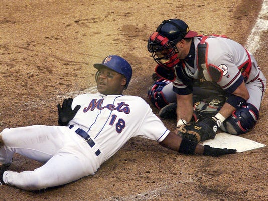 File photo of New York Mets Darryl Hamilton getting tagged out at the plate by Atlanta Braves catcher Javy Lopez in New York