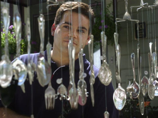 July 2000: Paul Mayer looks at spoon wind chimes made by Steven Manning of Ludlow, Vermont at the Corn Hill Arts Festival. Mayer is from Rochester. For Metro.