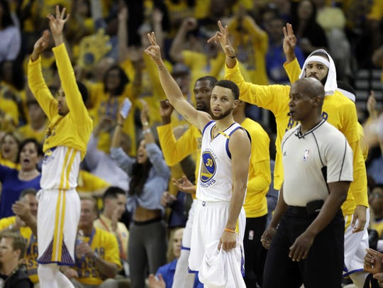 The Warriors celebrate a 3-point basket from the bench