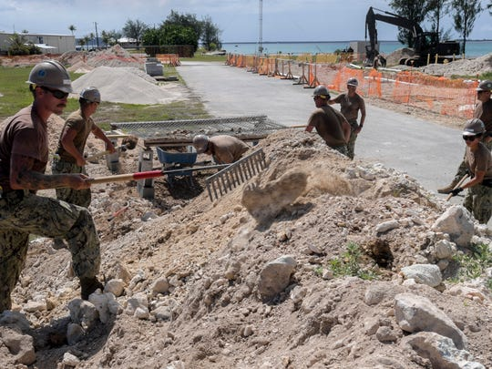 Builder 3rd Class Cooper Desario, assigned to Naval Mobile Construction Battalion (NMCB) 11, Det. Guam, removes a large rock from dirt to be sifted for the foundation of a restroom and shower facility at Polaris Point, April 5, 2018.