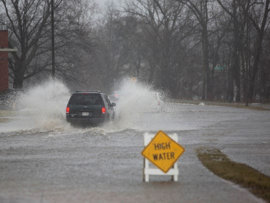 The driver of a car wades through an overflowing street