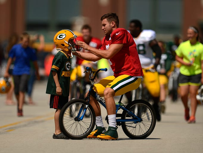 Green Bay Packers quarterback Chase Rettig lets a youngster wear his helmet to training camp practice on Tuesday, Aug. 5, 2014. Evan Siegle/Press-Gazette Media