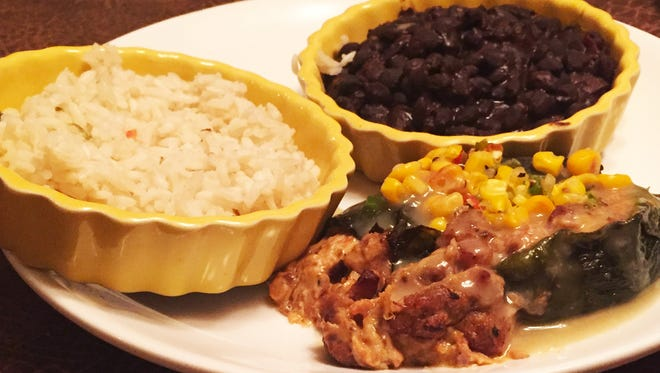 Stuffed poblano ($16), a roasted poblano pepper stuffed with slow cooked pork and pepper jack cheese topped with roasted corn sauce spicy confetti rice and house-made black beans.
