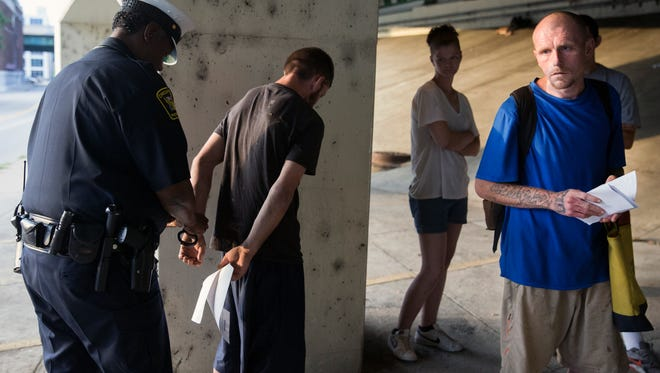 Justin Warfield, 30, along with several others, is rousted from their homeless encampment under the I-71 overpass at 550 Butler Street in downtown Cincinnati on July 12, 2017. Warfield first experienced with heroin when he was 14. By the time he was in his early 20's, he had a full-blown heroin addiction. At the time of this photo, he talked about wanting treatment, but not being able to navigate the system without a phone. Three days later, he was arrested on drug instrument charges. He's currently in the Hamilton County Justice Center and is expected to get treatment as part of his sentencing.