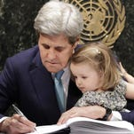 Secretary of State John Kerry, holding his granddaughter, Isabel Dobbs-Higginson, signs the Paris Agreement on climate change Friday at the United Nations.