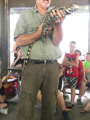 Natural Scott Shupe shows off a tegu lizard while discussing how snakes and lizards are both alike and different.