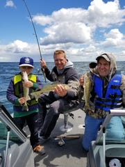 Nolan Kron, Kyle Johnson and Jim Kron holding walleyes