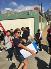 Rotary members from the Valley carry supplies to a middle school in Mexico that members helped paint.