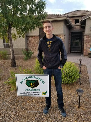 Ethan Pelland, a Basha High School student, poses in front of a sign that recognizes his academic achievement.