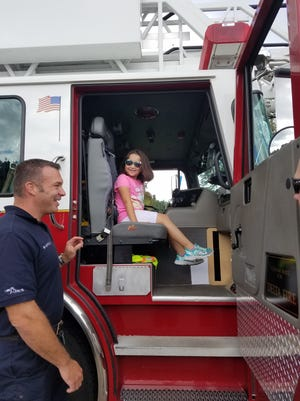 A child sits in a fire truck at Delta Township's Touch A Truck Day in 2017.