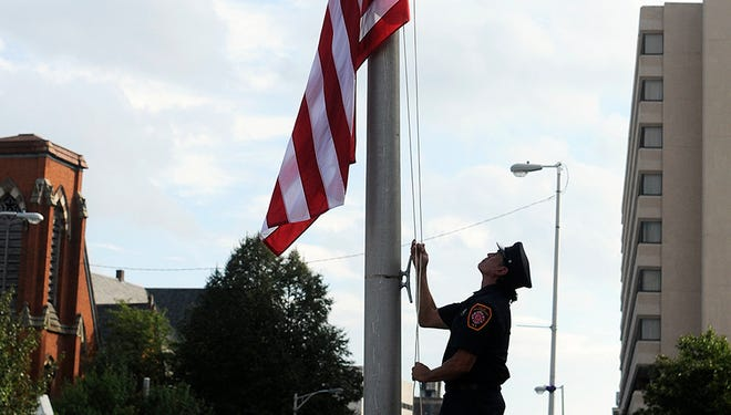 City of Poughkeepsie firefighter Jeff Morris lowers the flag to half-staff during September 11 memorial service Thursday at Poughkeepsie City Hall.