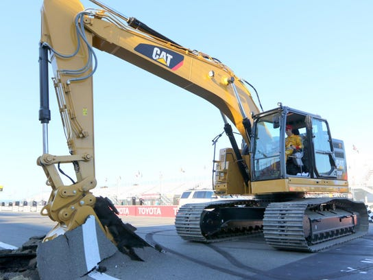 Joey Logano operates an excavator on the front straightaway