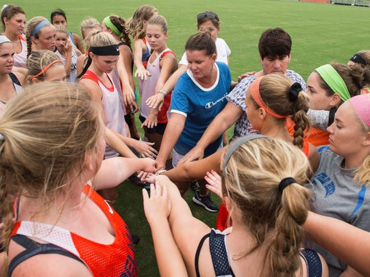 Delmar field hockey coach Jodi Hollamon, center, leads a team hand-stack after practice at Delmar Middle and Senior High School on Wednesday, Sept. 6, 2017.