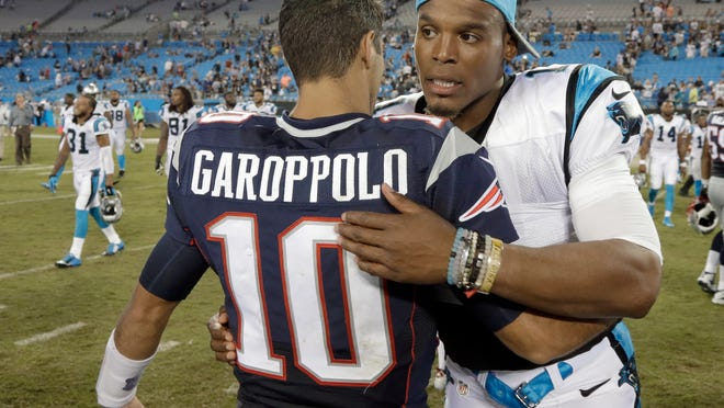 Former Patriots quarterback Jimmy Garoppolo, left, hugs then-Carolina Panthers QB Cam Newton after a preseason game in 2015. The two gunslingers will face each other Sunday, when Garoppolo leads the San Francisco 49ers against Newton and Patriots.