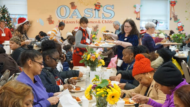 Women and children enjoy holiday meal on Wednesday, Dec. 21 at Paterson's Oasis social service program on Mill Street.