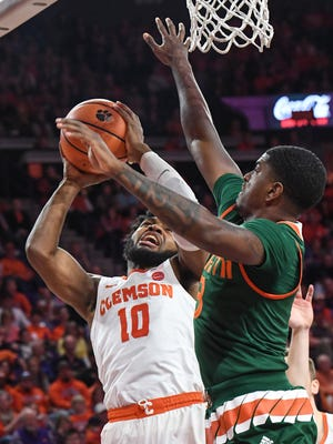 Clemson guard Gabe DeVoe (10) shoots near Miami junior Anthony Lawrence II(3) during the first half at Littlejohn Coliseum in Clemson on Saturday.