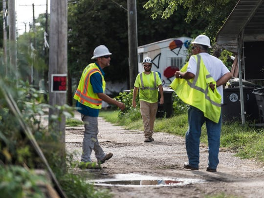 Environmental Quality Management workers finish working for the day at a lead cleanup site on a property in the 700 block of Gum Streetin Evansville, Ind., in July 2017.
