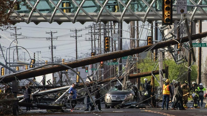 Two people were trapped in the car at center for more than an hour after several power poles came crashing down on East Marginal Way on Friday, according to Tukwila police. Their injuries do not appear to be life-threatening.