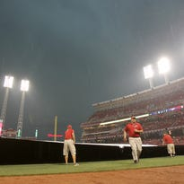 The Reds grounds crew covers the field following a rain delay in the third inning during the MLB game between the Cincinnati Reds and Cleveland Indians Friday, July 17, 2015, at Great American Ball Park in Cincinnati.