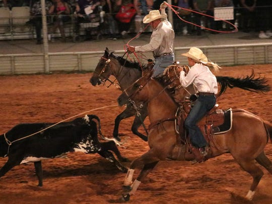 Kaitlyn Silva, front right, ropes a steer during the team roping event.