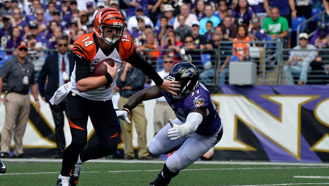Cincinnati Bengals quarterback Andy Dalton (14) stiff-arms Baltimore Ravens inside linebacker C.J. Mosley (57) as he runs during the first quarter at M&T Bank Stadium.