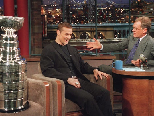 "Steve Yzerman, left, sits next to his his team's 1998 Stanley Cup as he appears with David Letterman during a taping of ""The Late Show with David Letterman"" on June 22, 1998."