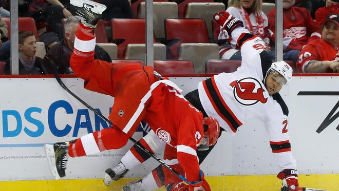 Detroit Red Wings defenseman Danny DeKeyser (65) checks New Jersey Devils right wing Devante Smith-Pelly (25) in the first period of an NHL hockey game, Tuesday, Jan. 31, 2017, in Detroit. (AP Photo/Paul Sancya)