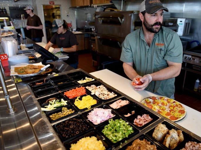 Bryan Begbie, co owner of Uncle Maddio's Pizza in Northshore Town Center, builds a customer's pizza Tuesday, August 16, 2016.