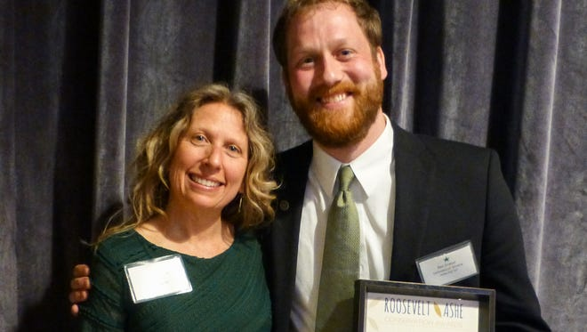 Tracy Davids, left, vice-president of the Wild South Board of Directors, presents Ben Prater with the inaugural Kayah Gaydish Award at the Wild South Green Gala May 7 in Asheville.