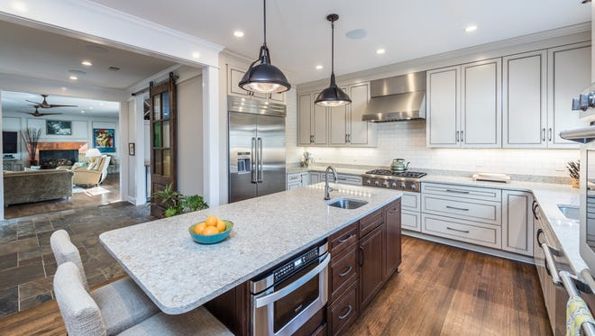 The openness of the house brought in more light. The Hayes opted for shaker style cabinets that go to the ceiling, bronze hardware and neutral, sandy granite counter tops.