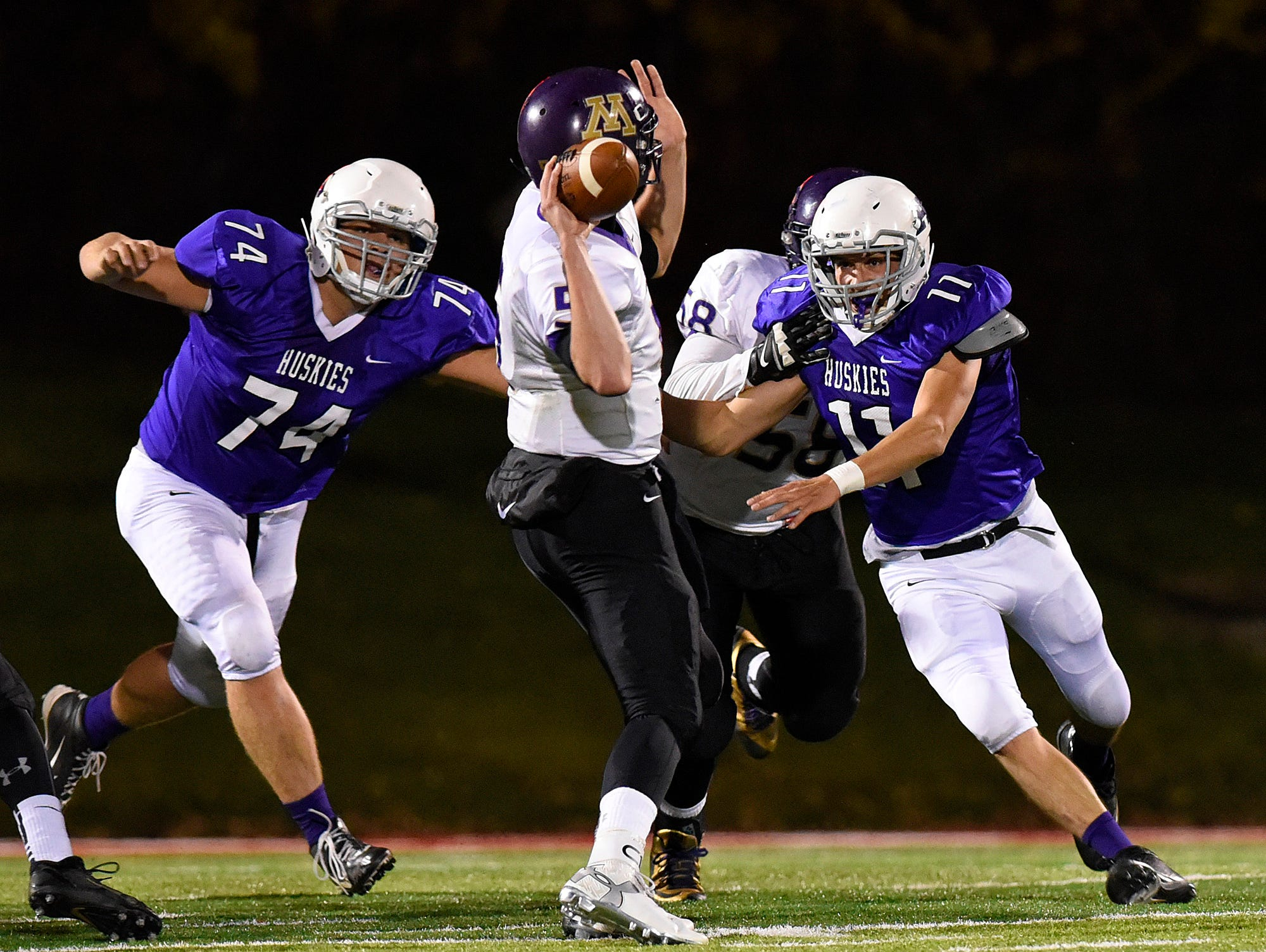 Albany's Brody Bierbaum (74) and Neal Anderson (11) set their sights on Montevideo's quarterback Troy Diggins during the first half Saturday, Oct. 24 at Husky Stadium.