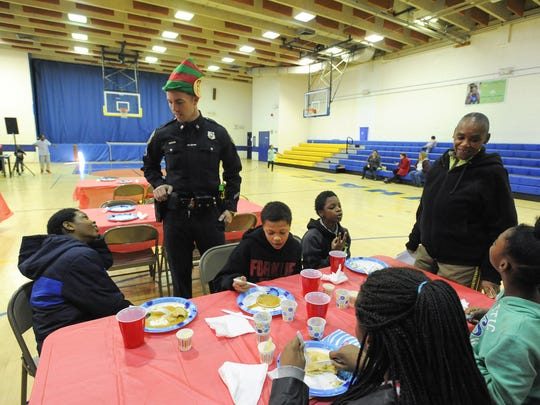 Former Wilmington Police Cpl. Thomas Oliver talks with kids who came to eat breakfast which the police department cooked at West Center City's Hicks Anderson Center in 2015.