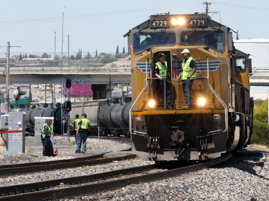 An El Paso police officer at left stands in the front of a train at the railroad crossing at San Marcial Street just South of Durazno Ave. in Central El Paso Sunday. According to police, a pedestrian was killed after being struck by a train in a fatal accident Sunday morning.