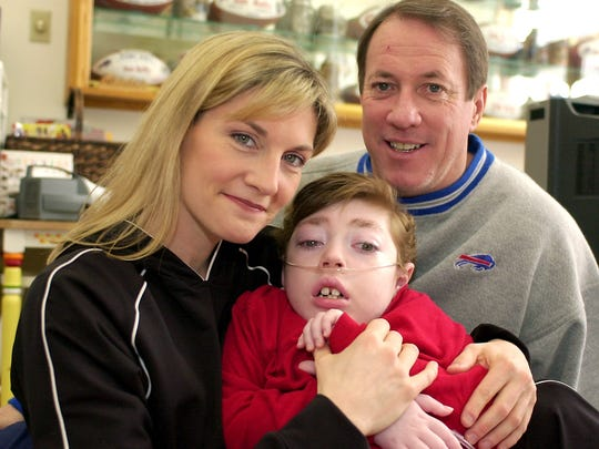 Hall of Fame quarterback Jim Kelly and his wife, Jill, pose for their portrait with son Hunter, 6, in Orchard Park on Feb. 10, 2004.
