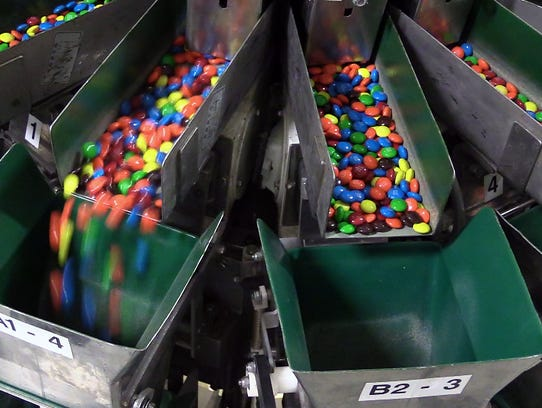 M&M's fall into a chute that sends them into individual packages at the Mars Chocolate plant in Hackettstown, N.J., on March 1, 2016.