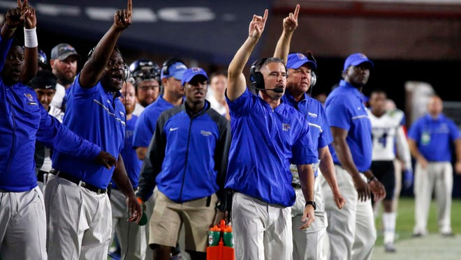 Memphis head coach Mike Norvell, in the front, leads his coaches in signaling a play during the second half of their NCAA college football game against Mississippi, Saturday, Oct. 1, 2016, in Oxford, Miss. Mississippi won 48-28. (AP Photo/Rogelio V. Solis)