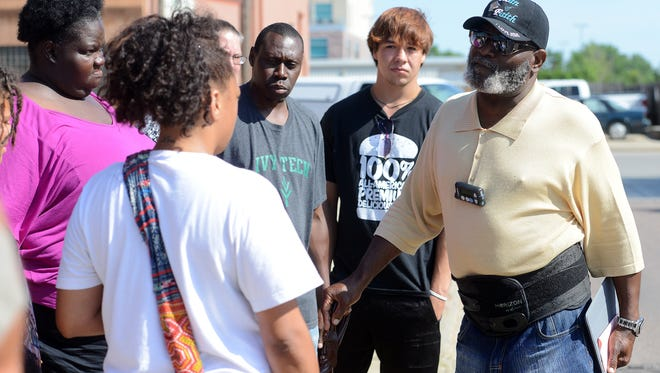 Floyd Pickett, right , talks with people outside of Josiah's Coffeehouse & Cafe Tuesday, July 28, 2015.