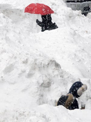 Commuters walk between piles of snow on a street in downtown Boston on Feb. 11, 2015.
