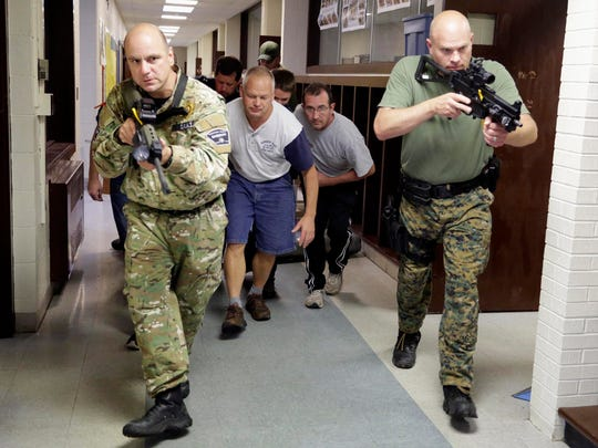 Sheboygan County SWAT team members protect first responders treating a 'victim' during a training session Tuesday, Sept. 8, 2015 at the former Willigen School near Haven.